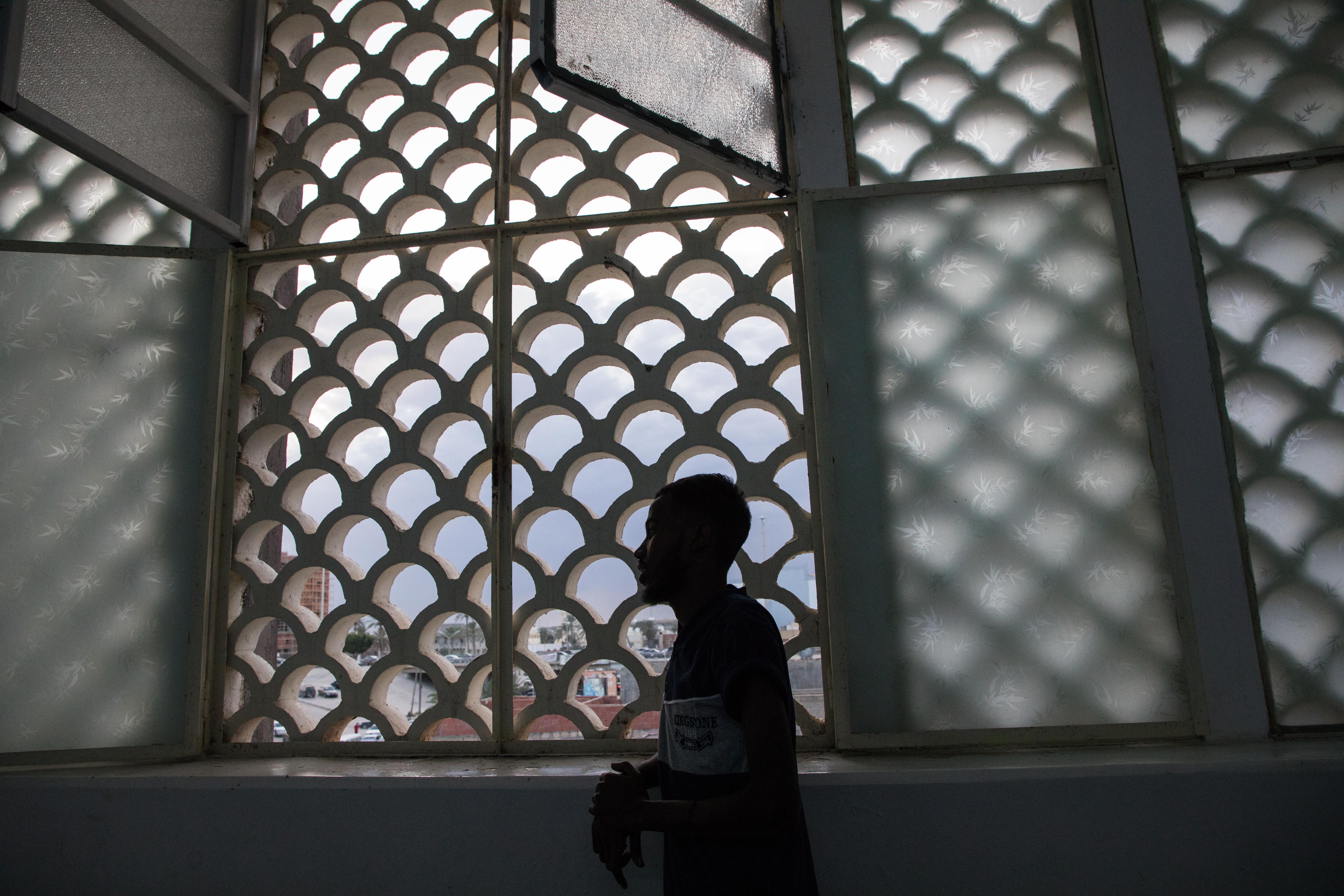 «En février dernier, les garde-côtes libyens ont rattrapé le bateau sur lequel j'essayais de quitter la Libye. Après l'arrestation, j'ai été conduit au centre de détention de Souk Al Khamis, dans la ville de Khoms. Mon nom est Youssef*, j'ai 21 ans et suis originaire de Mogadiscio, en Somalie. Des équipes du HCR sont venus nous voir à Souk Al Khamis et m'ont enregistré, j'attendais d'être transféré vers Tripoli. Quelques jours après, les gestionnaires du centre nous ont dit, à quelques Somaliens et moi-même, de monter à bord de 2 minibus. Enfin, nous allions être transférés. Ça, c'était ce que je pensais. Mais après plusieurs heures de bus, nous nous enfoncions de plus en plus dans le désert. C'est à ce moment-là que j'ai réalisé que nous ne roulions pas vers Tripoli, mais que nous risquions d'être vendus à des trafiquants. Ce risque s'est confirmé quand j'ai repéré des hommes armés qui s'approchaient à bord de leurs pick-up. Dans la hâte et la peur, nous avons tous décidé d'essayer de nous échapper par surprise, quitte à y perdre la vie. Au moins deux personnes sont mortes dans la fusillade qui a suivi.Je fais partie du groupe qui a réussi à fuir jusqu'à atteindre, à l'aube, une petite ville dont je ne connais pas le nom. Là-bas, un vieil homme libyen nous a offert de quoi boire et de quoi manger, et il est allé avertir les autorités de notre présence. On nous a emmenés au centre de détention de Sirte–nous y sommes restés 5 mois. Les équipes de MSF qui nous connaissaient à Souk Al Khamis sont venues plusieurs fois nous voir à Sirte pour soigner ceux qui étaient malades. Ensuite, nous avons été envoyés dans une autre prison, à Misrata. C'était vraiment la pire. Je ne me sentais pas bien et MSF m'a fait venir à l'hôpital pour me soigner de la tuberculose. J'ai appris que le centre de détention de Misrata a fermé et que le groupe avec lequel j'ai survécu à cette aventure a dû aller à Souk Al Khamis, là où on a essayé de nous vendre… Retour à la case départ.»Youssef*, 