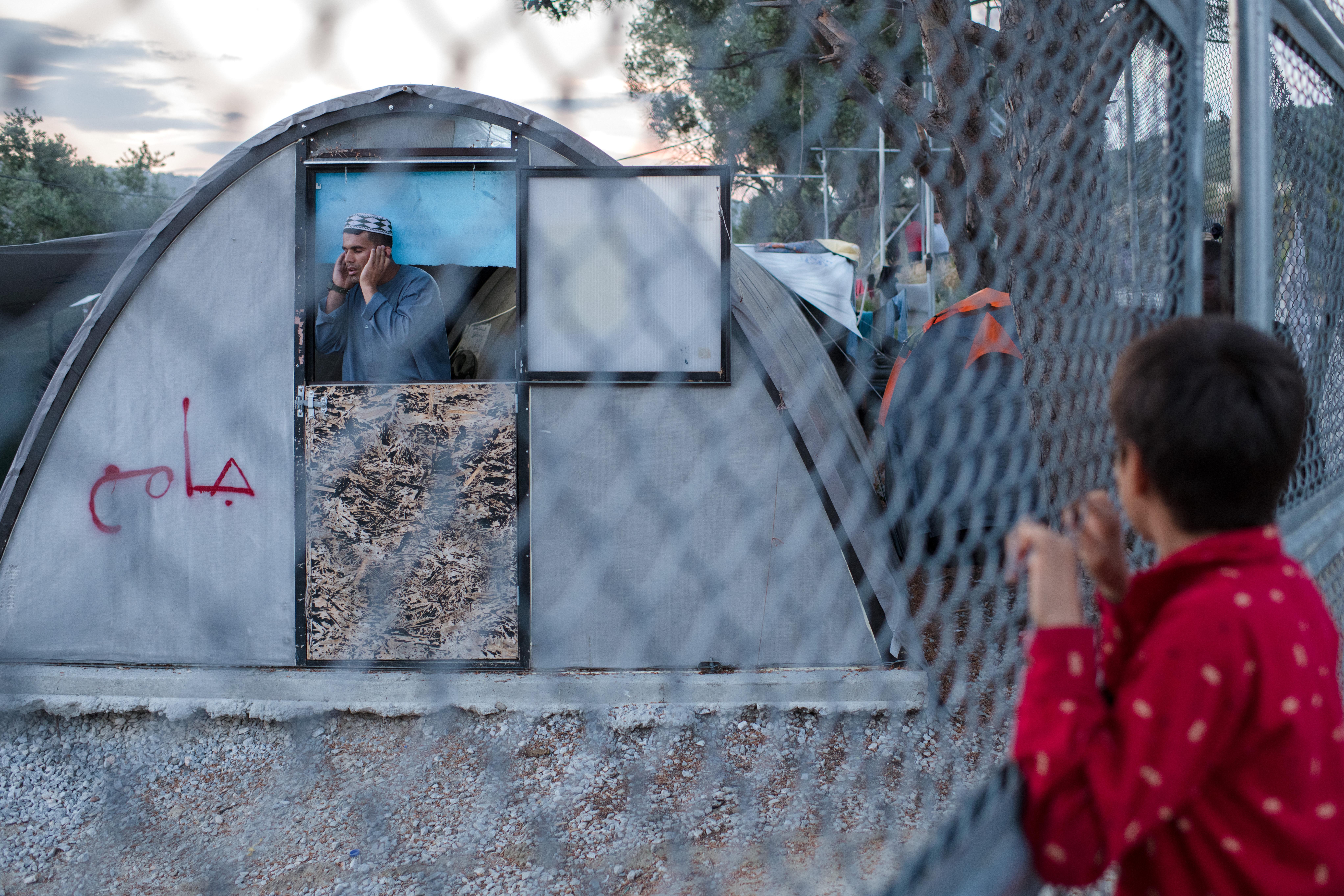 Un enfant regarde un bâtiment qui fait office de mosquée dans le camp de Moria, mai 2018. ©Robin Hammond/Witness Change