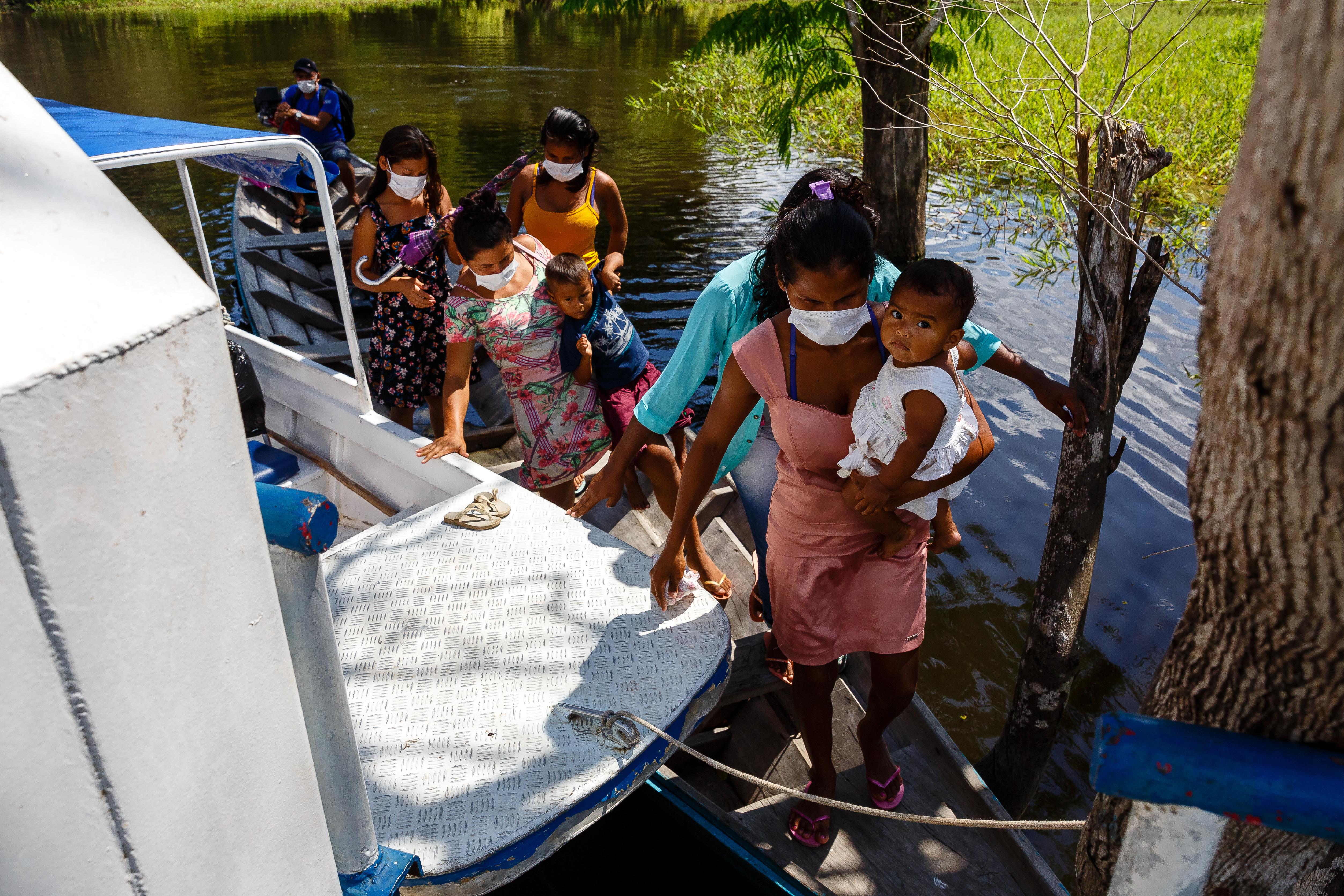 (haut) Les équipes MSF quittent le bateau-clinique pour effectuer le dépistage et les vaccinations de routine, de maison en maison, État d'Amazonas, Brésil, juillet 2020. (bas) La population locale arrive au bateau-clinique pour recevoir des soins. L'équipe MSF a aidé à aménager le circuit des patients et a améliorer les protocoles de prévention et de contrôle des infections pour réduire le risque de contamination, État d'Amazonas, Brésil, juillet 2020. © Diego Baravelli/MSF
