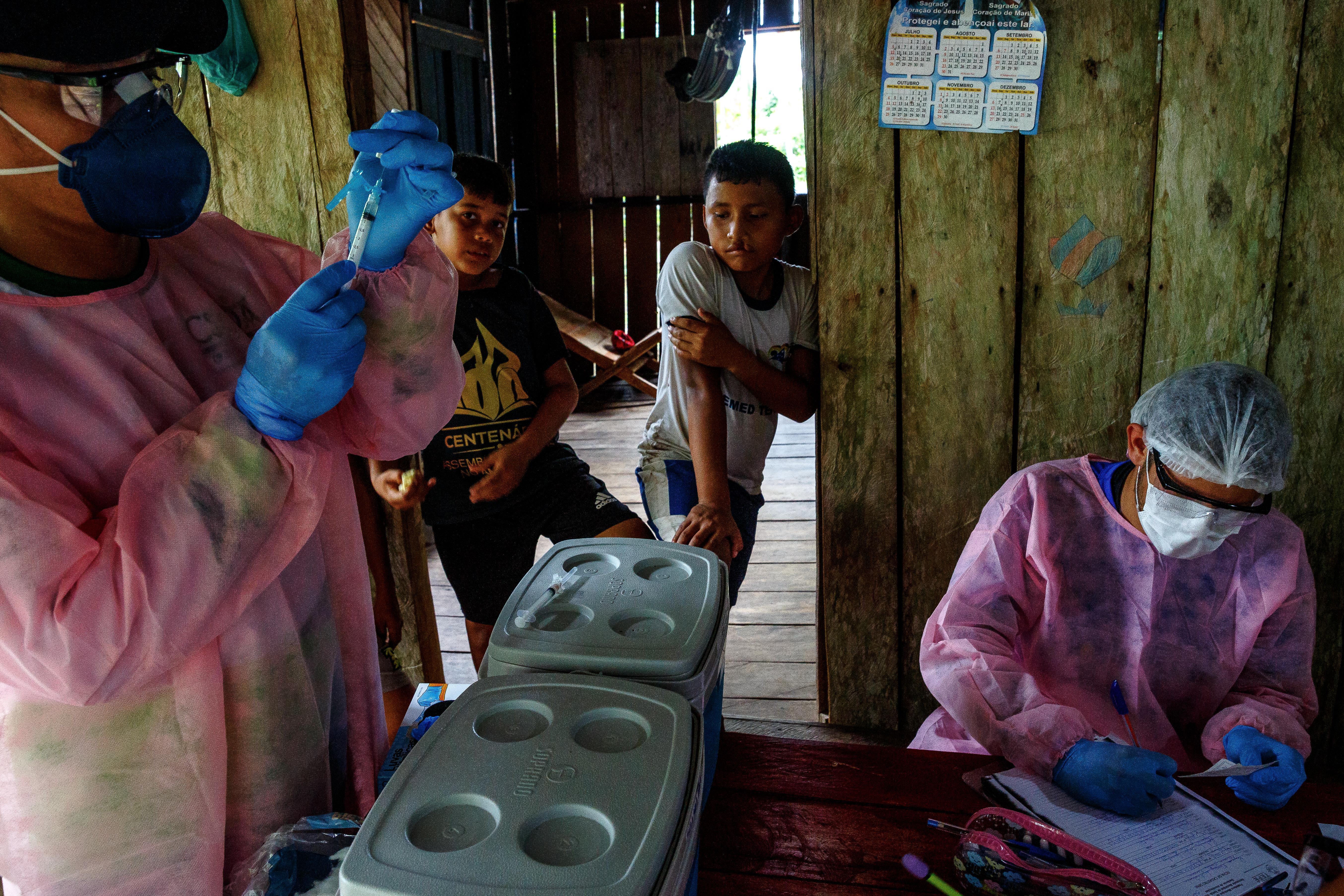 Le personnel MSF effectue des vaccinations de routine dans une maison familiale au bord du lac Mirini, État d'Amazonas, Brésil, juillet 2020. © Diego Baravelli/MSF