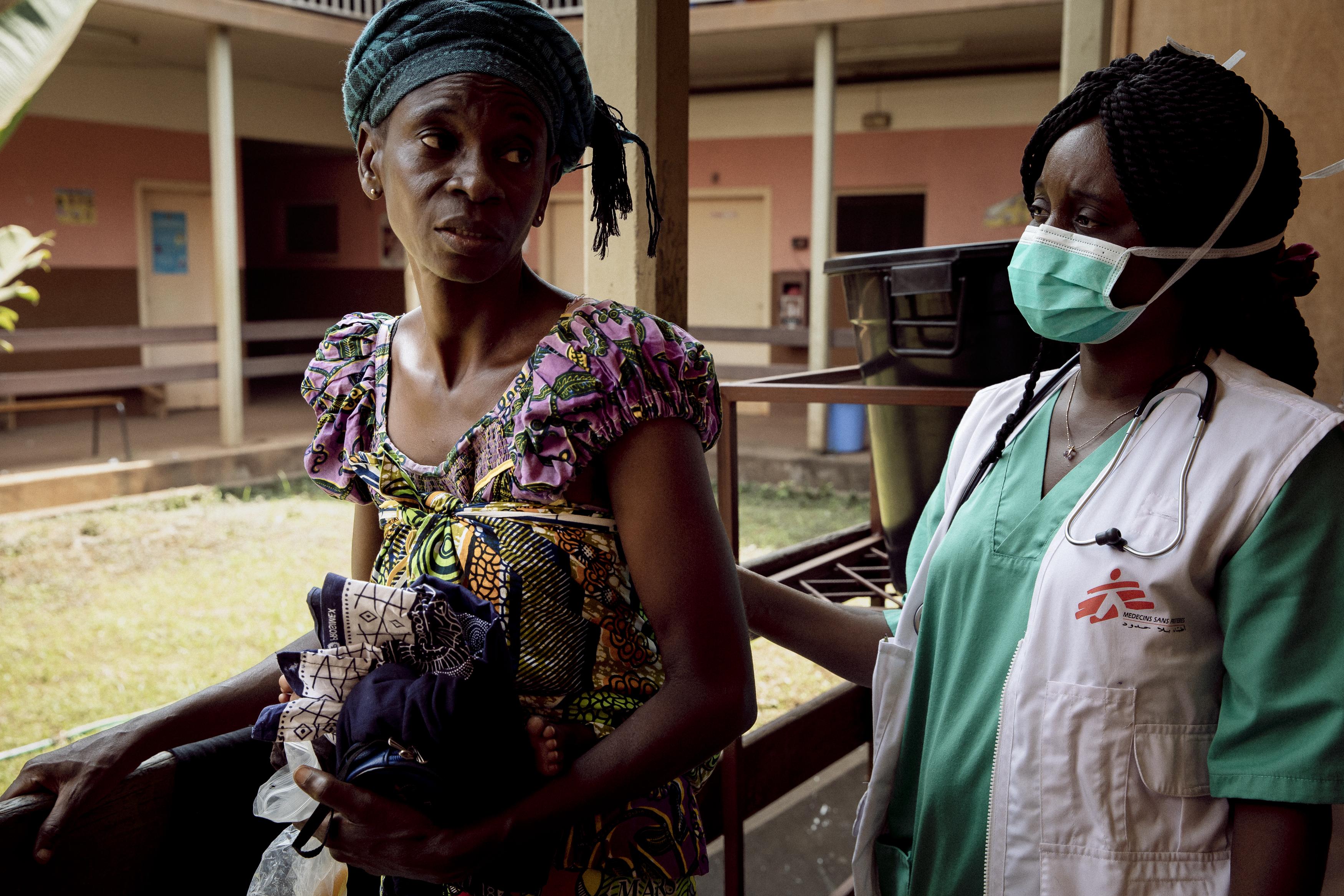 Hortense s'entretient avec le Dr Gertrude Komoyo à l'hôpital communautaire de Bangui le 25 novembre 2020. Sa fille est à l'hôpital depuis une semaine. Elle est devenue séropositive à 3 ans, lorsqu'elle a reçu deux transfusions de sang à la suite d'une anémie. Une fois testée, elle a commencé son traitement à l'âge de 9 ans.Crédit : Adrienne Surprenant/Collectif Item